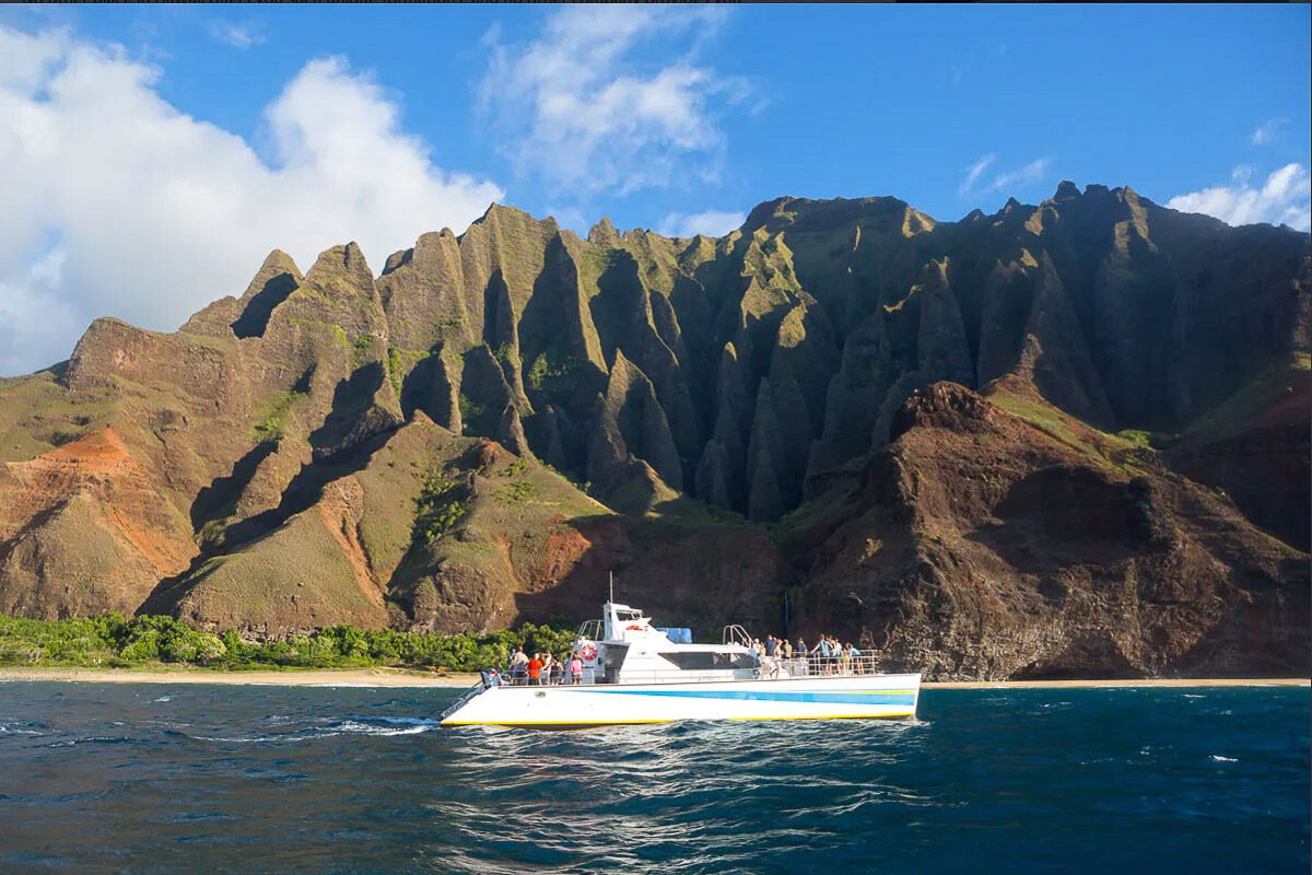 View of a small day-cruise boat with beautiful Hawaiian mountains in the background