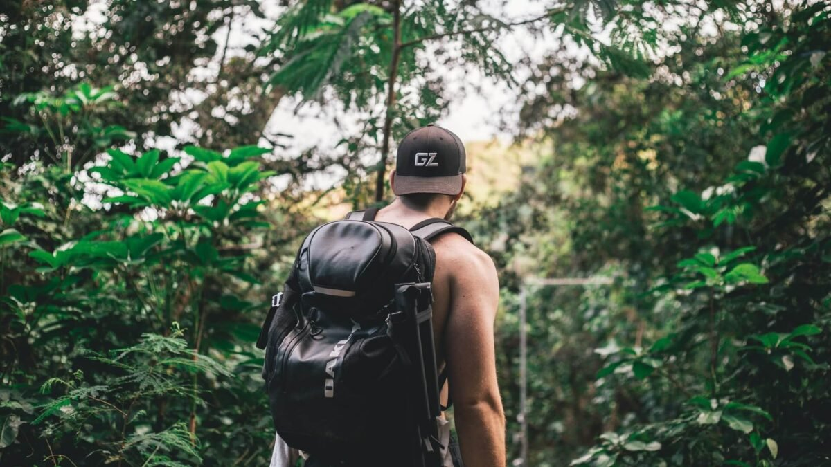 Back view of a man with a backpack walking through a jungle