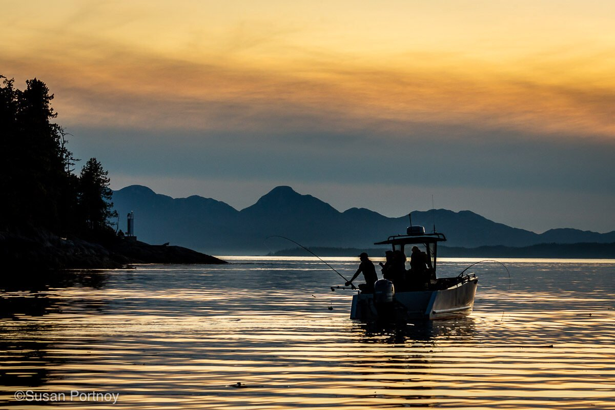 Silhouettes of people fishing off a boat, and the silhouette of mountains behind them at sunset