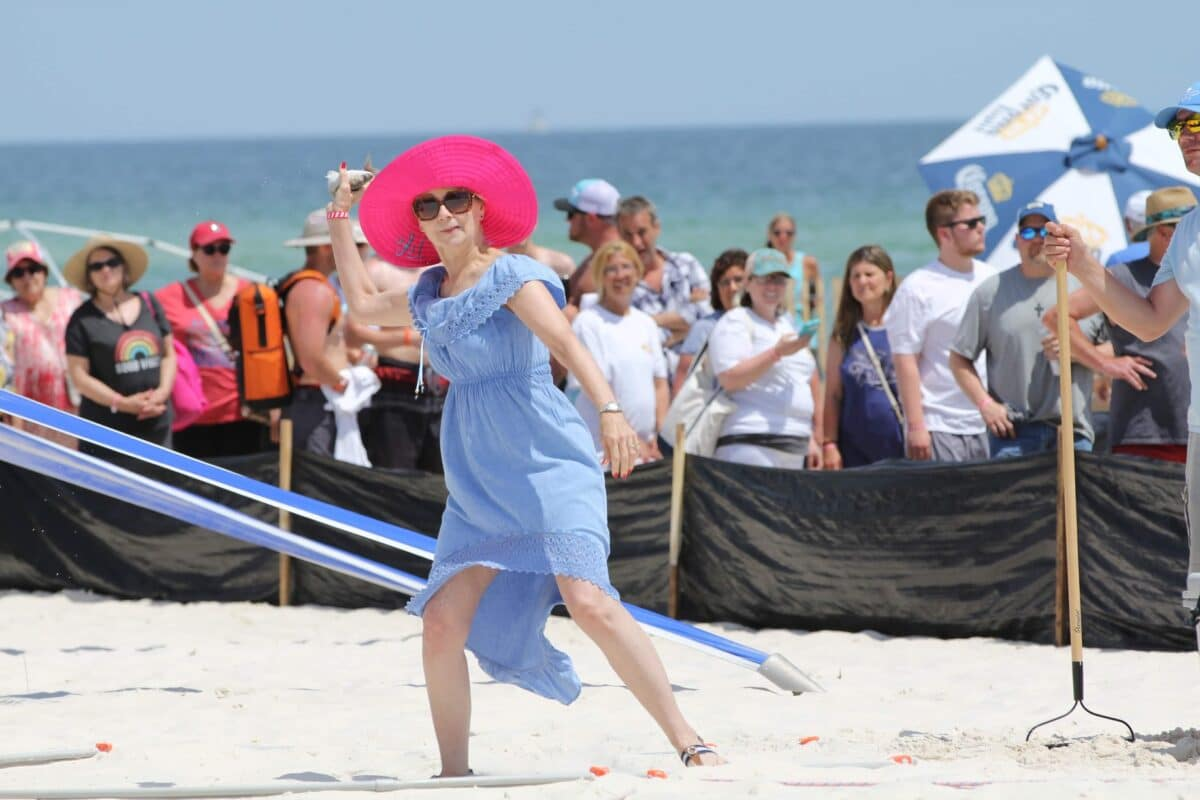 A woman wearing a blue dress and large red hat stands in the sand about to toss a mullet as far as she can.