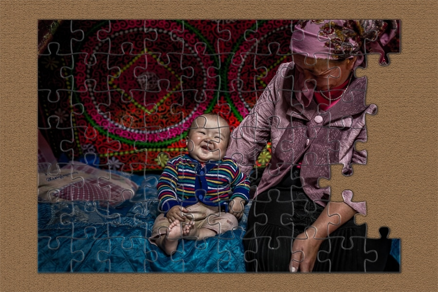 Puzzle - Mongolian baby laughing on a bed with his grandmother
