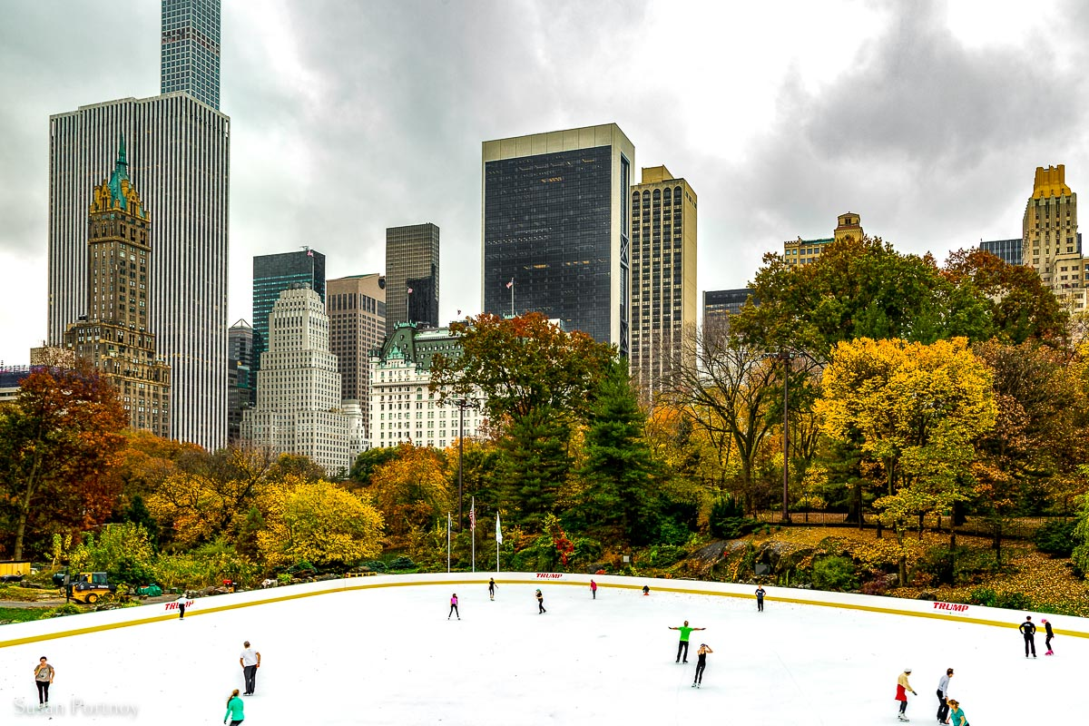 Ice skaters on Wollman Rink with New York City skyscrapers in the background, and colorful autumn leaves