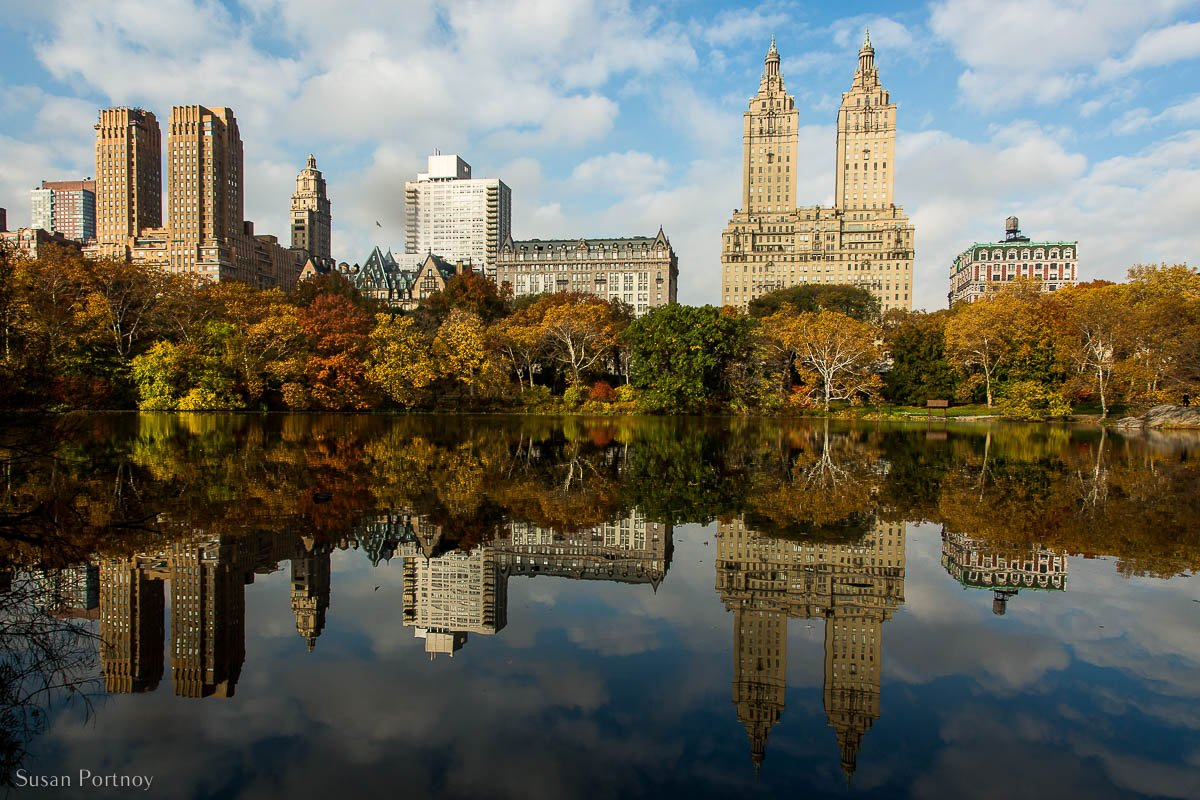 A spectacular reflection of the residential buildings on the west side of the The Lake in Central Park in fall