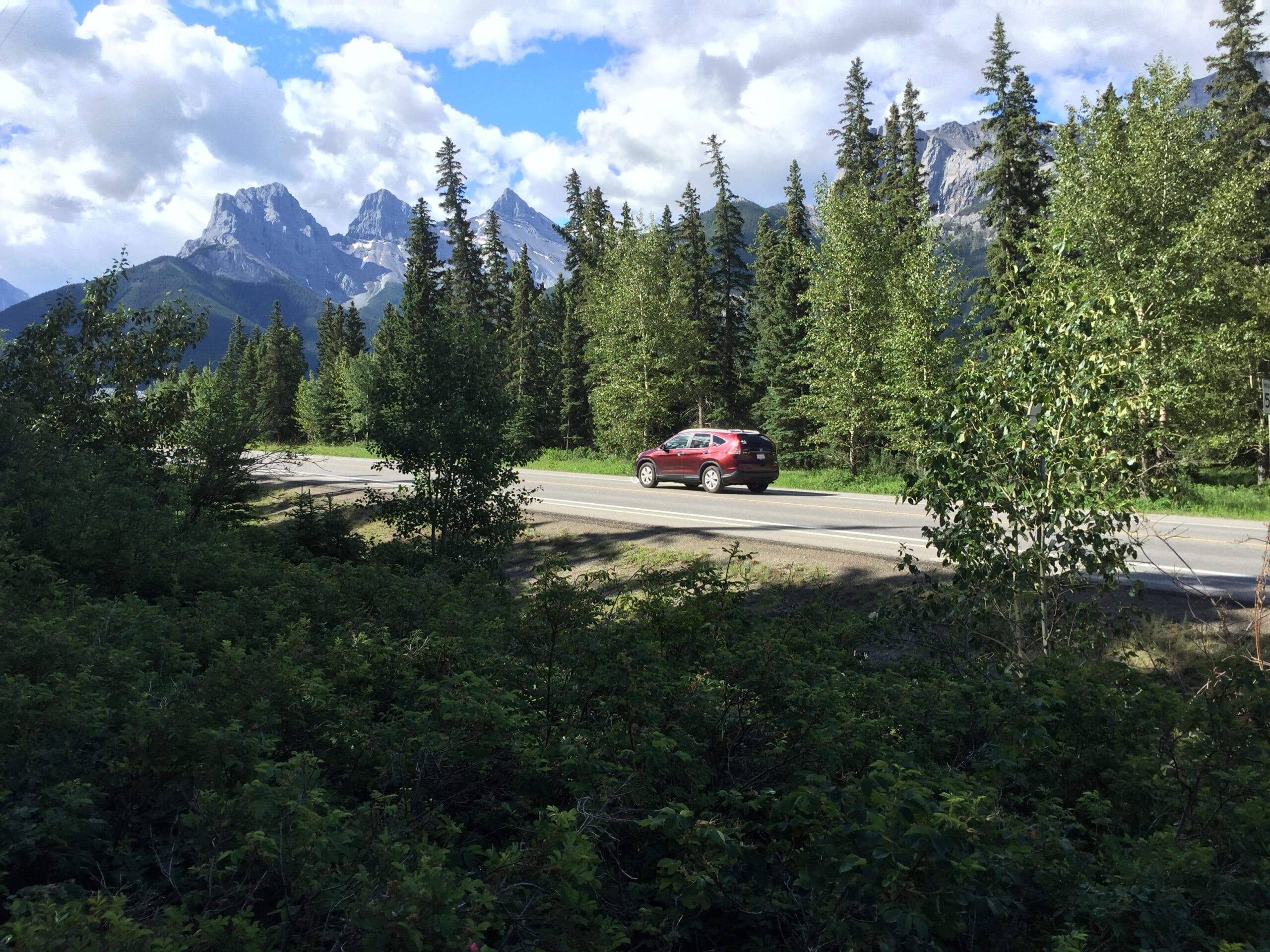A small red car drives  through Canmore, Alberta