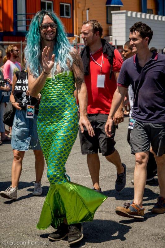 A bearded man dressed in a green mermaid dress with aqua hair walks in the Coney Island Mermaid Parade