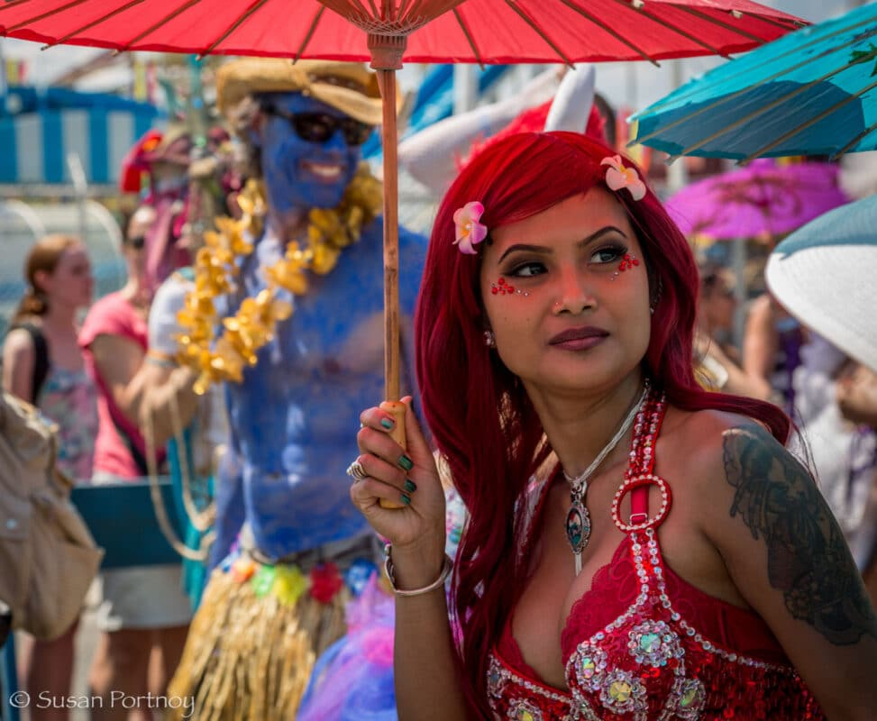 A woman wearing a red mermaid outfit holding a matching parasol walks in the Coney Island Mermaid Parade