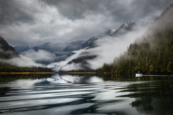 A breathtaking view of a small tender cruising on a rainy day on a lake surrounded by mountains and fog in the BC Rainforest