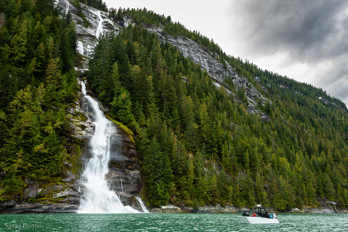 A 10-person tender in front of a large waterfall in the Great Bear Rainforest