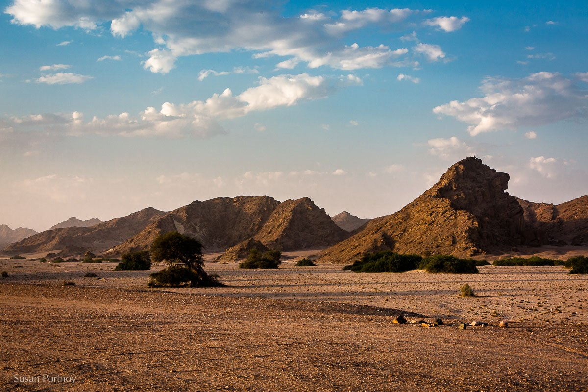 A landscape view of a desert with rock mountains and a blue sky in Namibia
