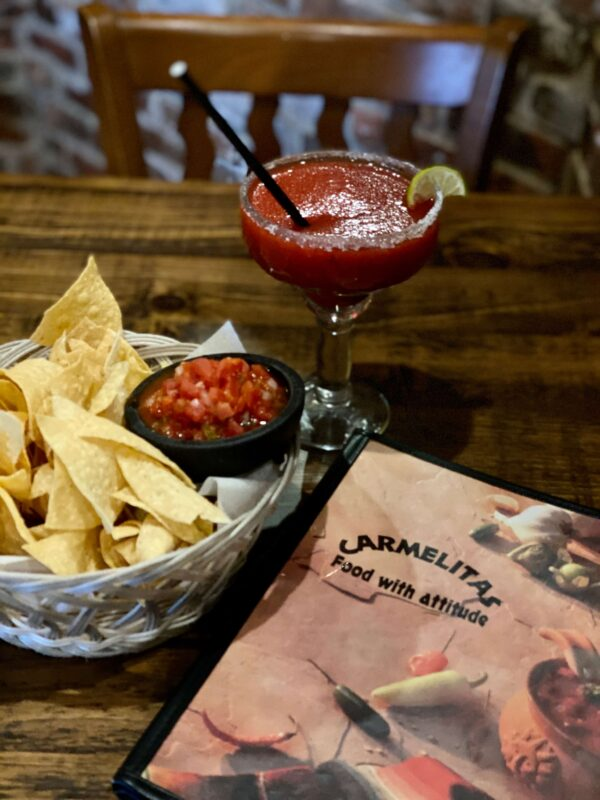 A Bowl of chips and salsa, next to a Carmelita's menu and a raspberry