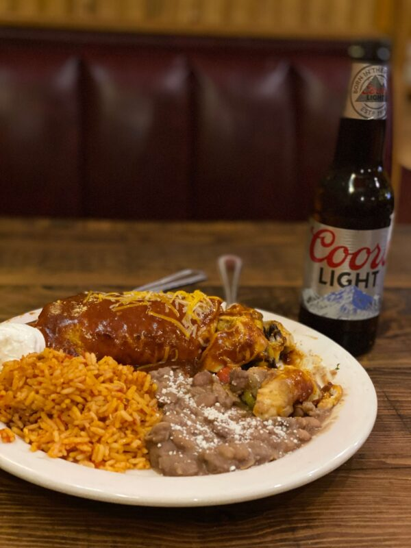 Enchilada with rice and refried beans, and a bottle of Coors at - Carmelita's Restaurant