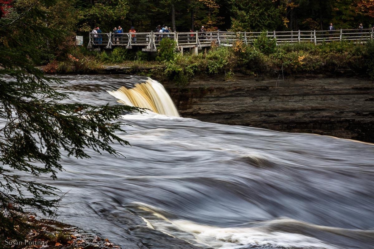 Upper falls and people standing on the viewing platform reached through the Tahquamenon State Park