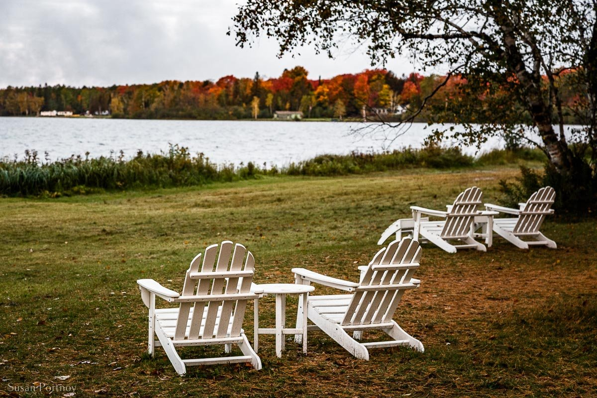 Lounge chairs on the lawn of Birch Lodge in Trout Lake, Michigan facing Mi Fall colors around the coastline