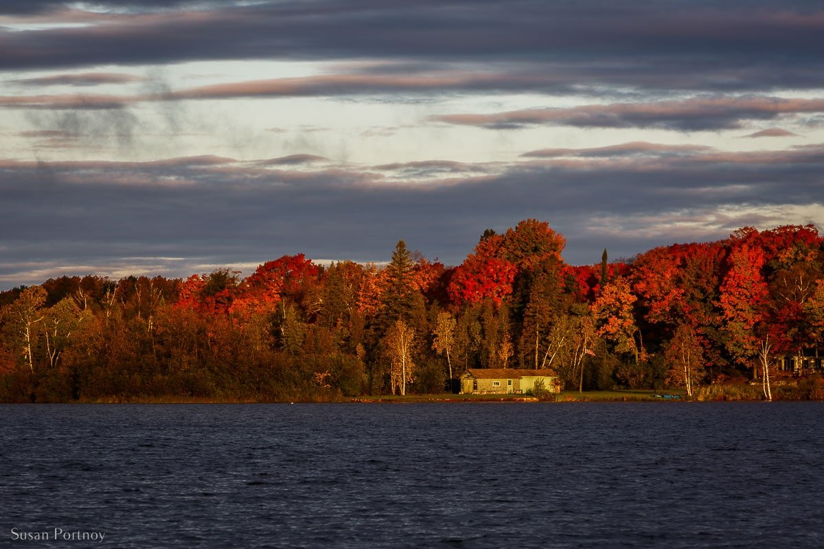 A gorgeous view of Michigan's fall colors at sunrise from the dock at Birch Lodge
