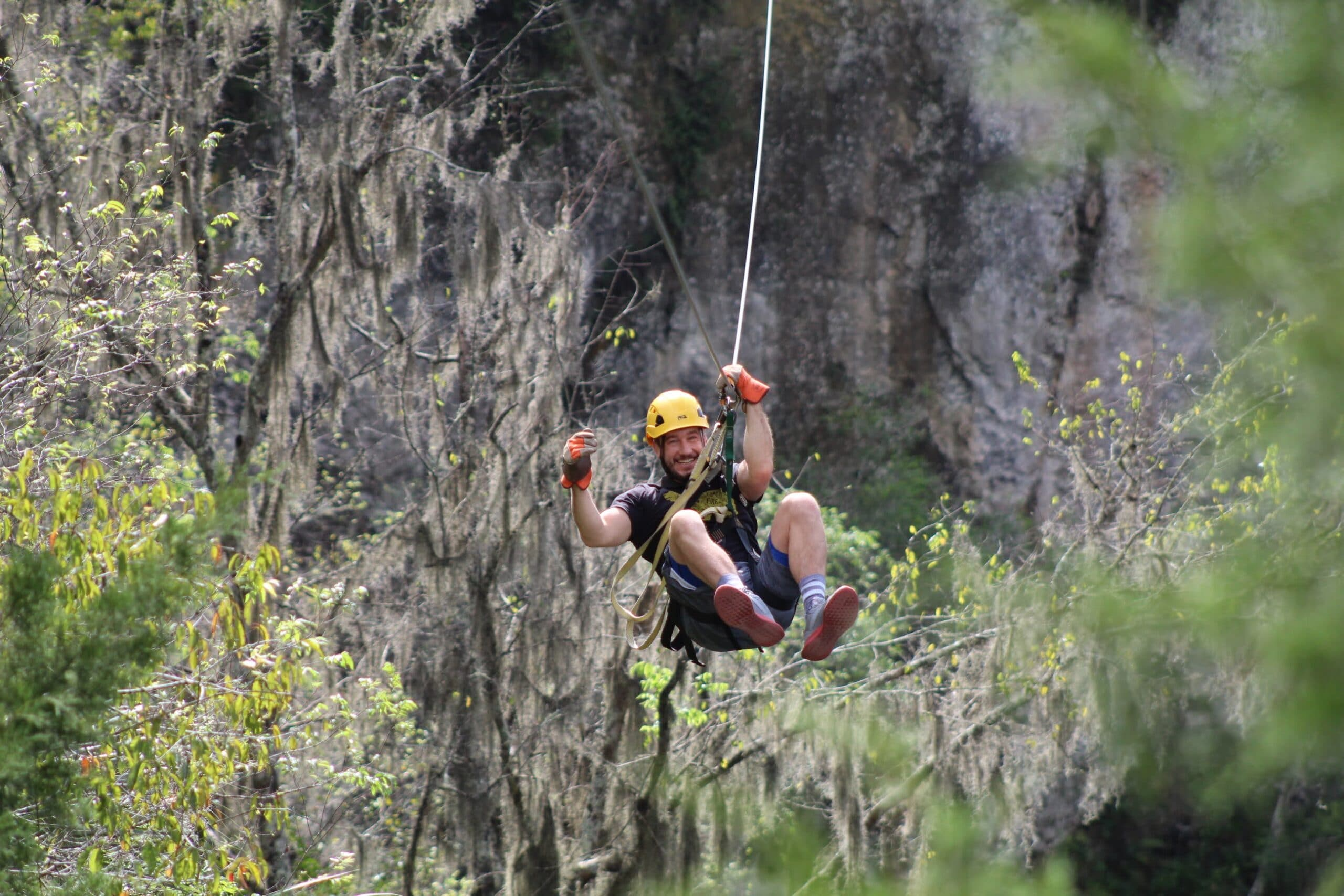 Our guide zip-lining over the canyon_courtesy of The Canyons Zip Line and Adventure Park, one of the cool things to do in Florida