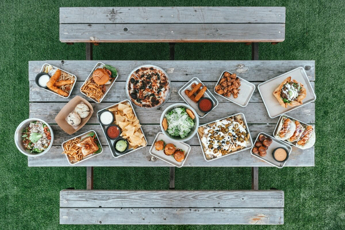 Top view of a picnic table loaded with food. Reusable plates and cutlery are essential on a road trip