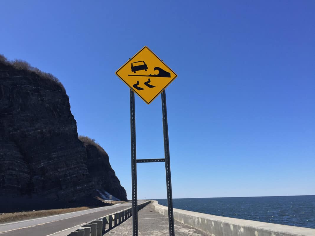 A highway sign warning of waves on the road Gaspé Peninsula, Quebec