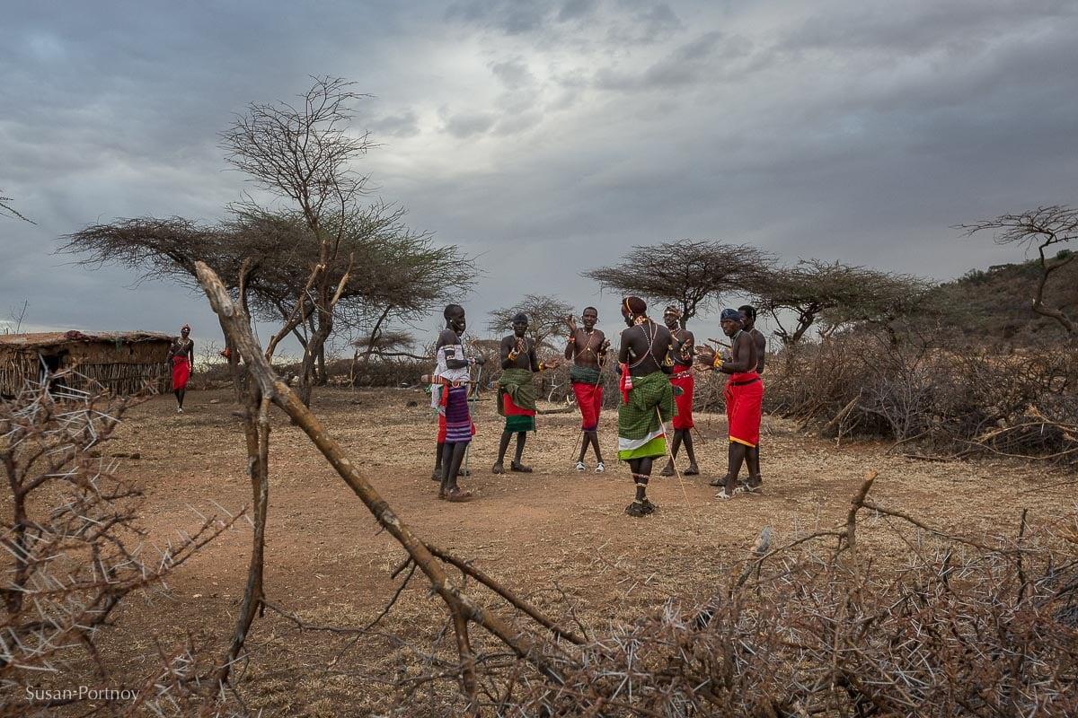 Samburu moran dancing in a circle in the middle of a manyatta in Kenya