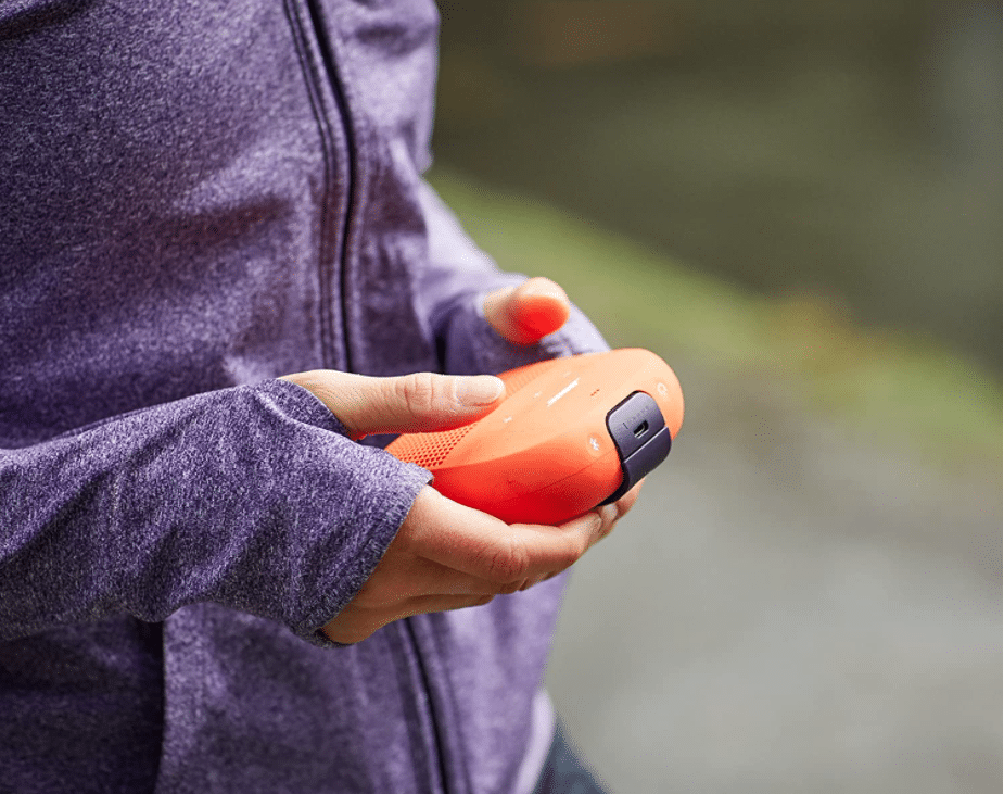 Woman holding an orange Bose SoundLink Micro, Portable Outdoor Speaker