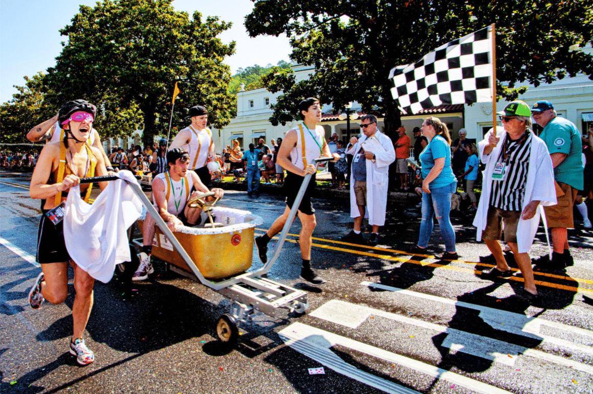 Contestants on the street in a bathtub on wheels Stueart Pennington World Championship Running of the Tubs.