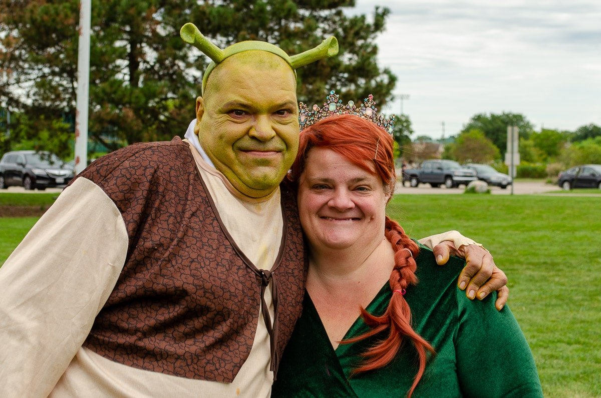 A portait of a man and woman dressed up as Shrek and Fiona from the movie