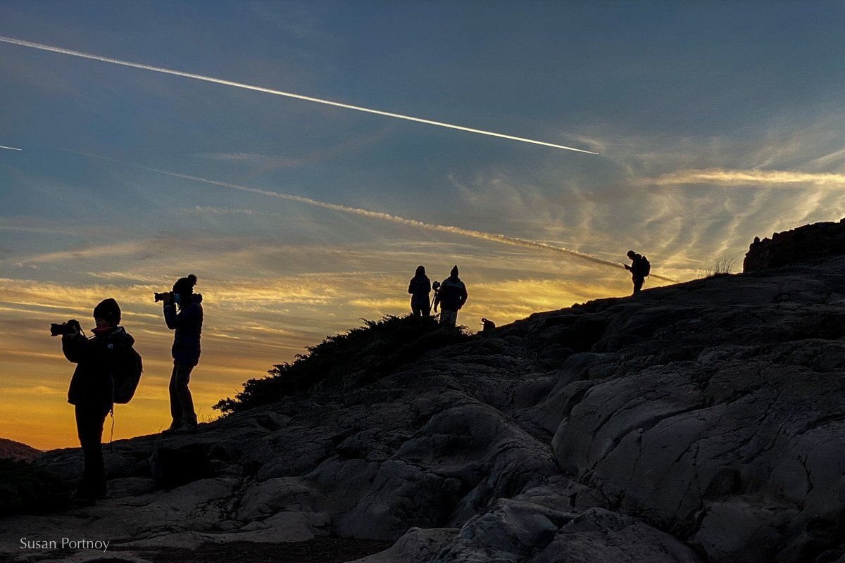 Silhouettes of photographers standing on an escarpment facing west at sunset