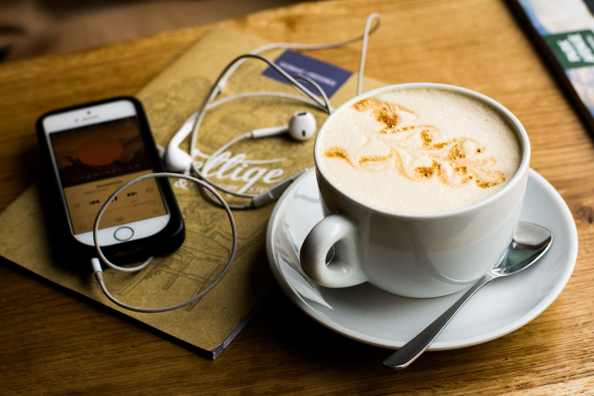 A cup of cappuccino on a table with a smartphone and earplugs