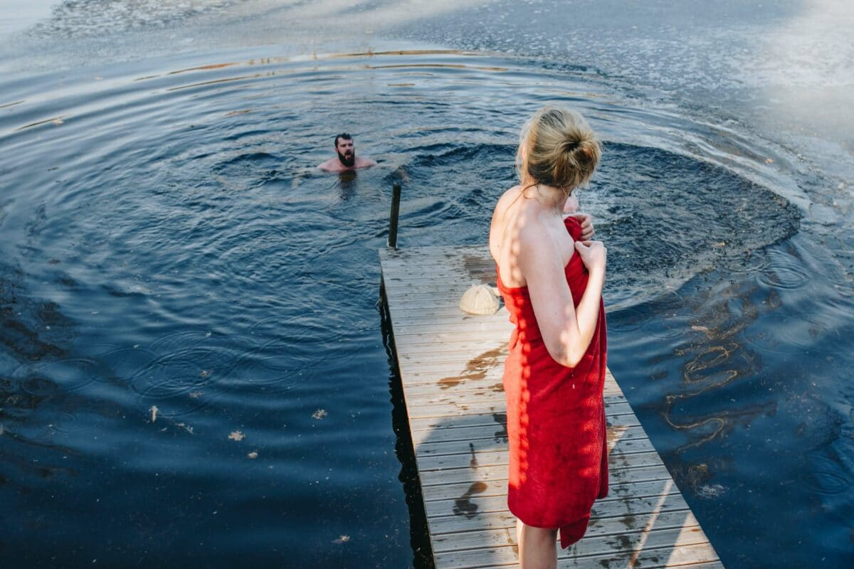 A man in the water on a lake while a woman in a towel she packed for her road trip is watching
